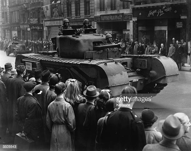 A crowd watching a 'Churchill' tank passing Fleet Street during the 'Salute A Soldier' march