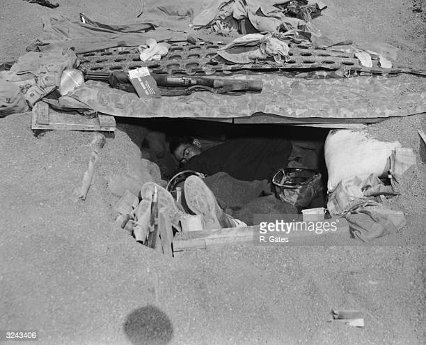 A United States Marine sleeps under an army blanket in his foxhole dug in the sand at the beach at Iwo Jima during World War II Japan The camouflaged...