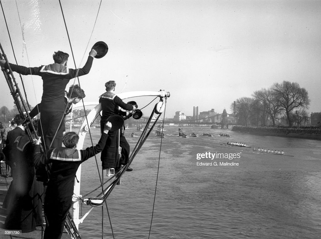 Cadets on board the training ship 'Stork' cheer as the Cambridge University rowing team lead Oxford by three lengths during the University Boat Race on the Thames.
