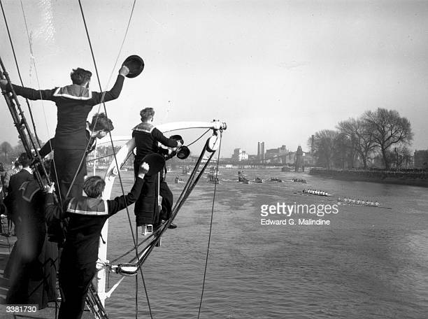 Cadets on board the training ship 'Stork' cheer as the Cambridge University rowing team lead Oxford by three lengths during the University Boat Race...