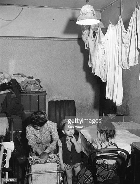 A mother with her three children living in squalid conditions washing drying on the line at Jubilee Buildings in Wapping a slum building in East...