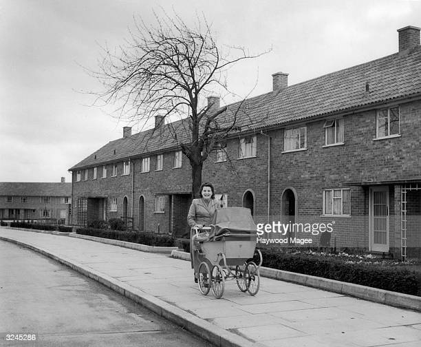 A woman pushes a pram past a row of council houses in the Adeyfield district of Hemel Hempstead a new town in Hertfordshire Original Publication...