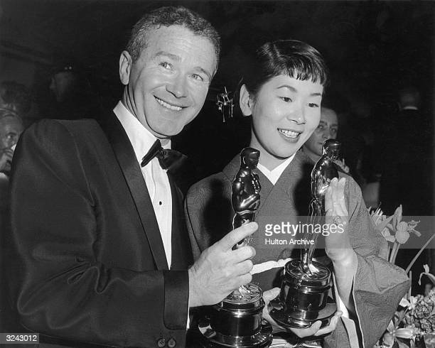 American comic actor Red Buttons and Japanese actor Miyoshi Umeki hold their Academy Awards for Best Supporting Actor and Actress which they won for...