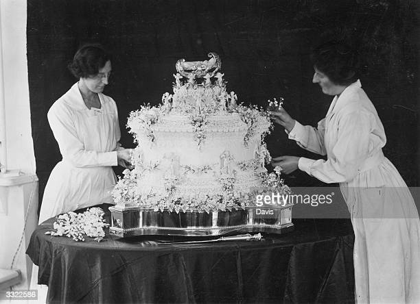 Two confectioners putting the finishing touches to a large cake celebrating the birth of Princess Elizabeth to the George Duke of York and Elizabeth...