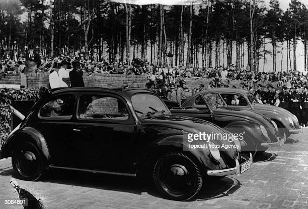 Three Volkswagen 'People's Cars' at a ceremony at which Adolf Hitler laid the foundation stone of a Volkswagen factory at Fallersleben The car is to...