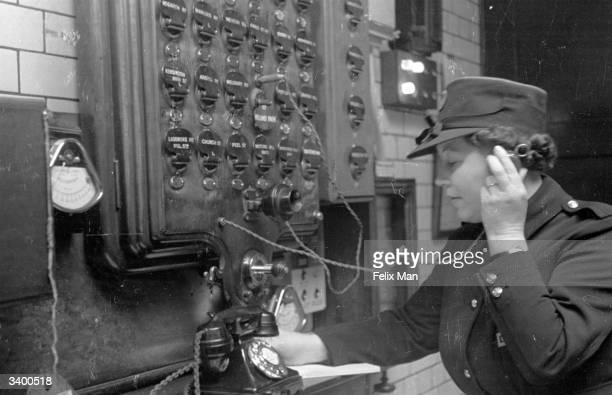 Women's Auxiliary Fire Service officer fielding calls on a switchboard at her fire station. She and her colleagues have volunteered for service to...