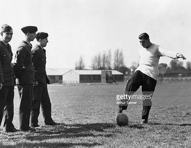 England and Arsenal centreforward Ted Drake is showing how to take a penalty kick to RAF recruits in his new role as a PT instructor in the Airforce
