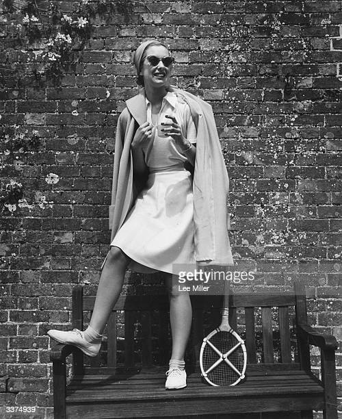 A tennis outfit consisting of a kneelength white flannel skirt and an openneck shirt Worn under a daffodil yellow coat which is worn loose the outfit...