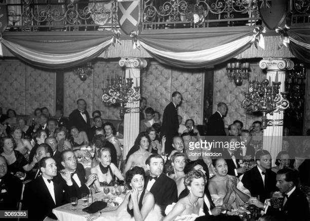 Movie stars Humphrey Bogart Lauren Bacall James Mason and Jennifer Jones spend a night out at the Cafe de Paris with entertainer Josephine Baker and...