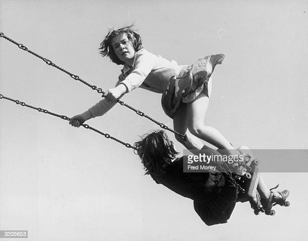 Maureen Hallahan and Marion Smith wearing rollerskates on the swing in the Welwyn children's recreation ground during the Whitsun Holidays