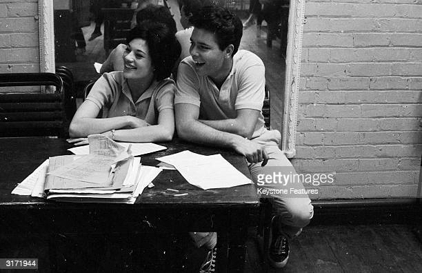 Cliff Richard and Carole Grey sit at a table strewn with pages of script, during a break from dance rehearsals for 'The Young Ones', directed by...