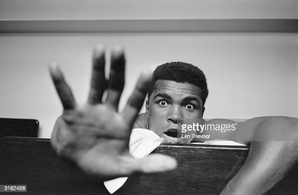 American Heavyweight boxer Cassius Clay lying on his hotel bed in London. He holds up five fingers in a prediction of how many rounds it will take...