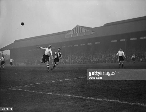 Fulham's centre-half beats Smith, the Newcastle United centre-forward, in a duel for the ball during a match at Fulham's Craven Cottage ground.