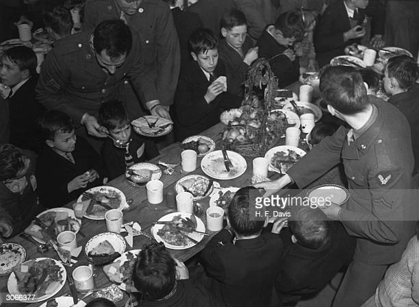 Two American airmen wait on their young British guests during a Thanksgiving party Instead of spending the festival in the usual way US troops in...