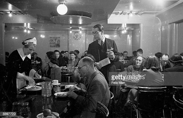 Frank Phillips News Reader looking for a place to sit at the crowded BBC canteen Original Publication Picture Post 1583 At The BBC Canteen pub 1943