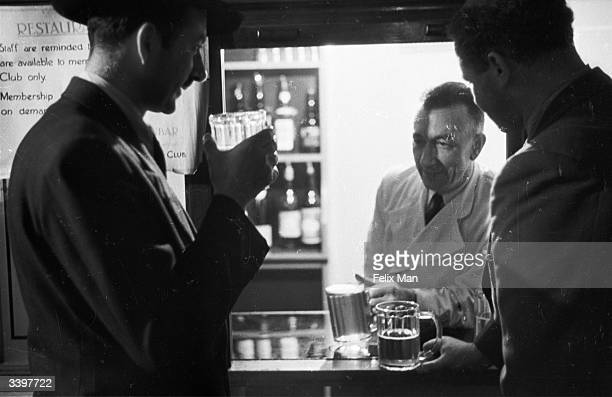 Laurence Gilliam Director of Features buys a drink for Colin Wills the Australian broadcaster at the BBC bar Original Publication Picture Post 1583...