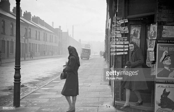A woman waits for her friend to come out of the newsagents as they make their way to work along the streets of Leicester on a chilly morning Original...