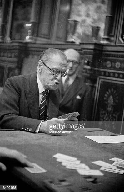 English novelist William Somerset Maugham the guest of honour at a bridge party at Crockford's Club contemplates his hand Original Publication...
