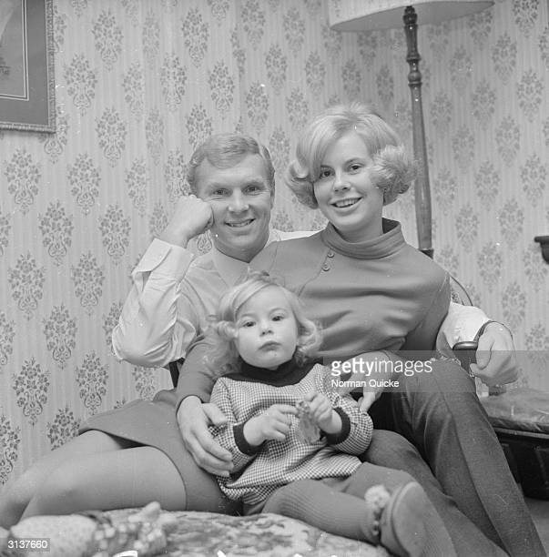 English footballer Bobby Moore at home with his wife Tina and his baby daughter Roberta