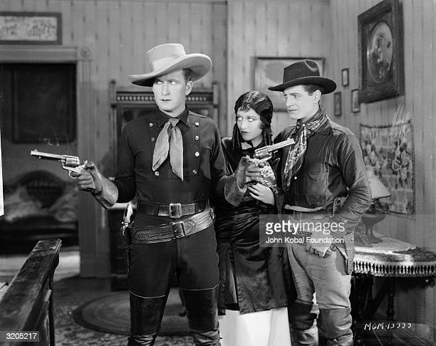 From left to right Tim McCoy Joan Crawford and Rex Lease in 'The Law of the Range' directed by William Nigh for MGM