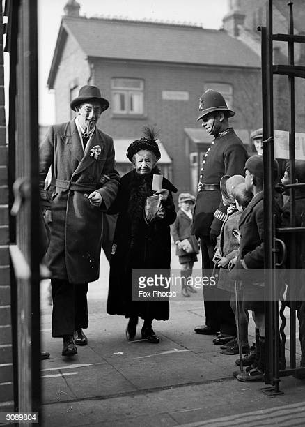 Mr Bell the Labour candidate for Wood Green in London escorts 92yearold grandmother Mrs Harradine into the polling station at Lordship Lane School to...