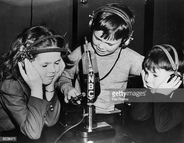 British evacuee 9-year-old Rona Whittaker and her two brothers Allan, aged 5, and Neville, aged 7, communicating with their parents in a two-way...