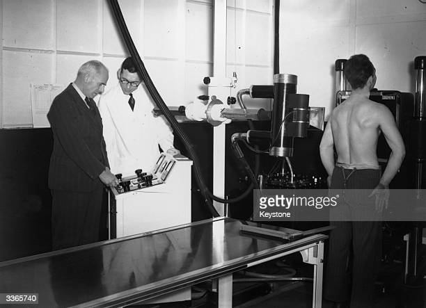 UnderSecretary of the Ministry of Health Sir William Douglas taking the first radiograph in a scheme to monitor Britain's factory workers for...