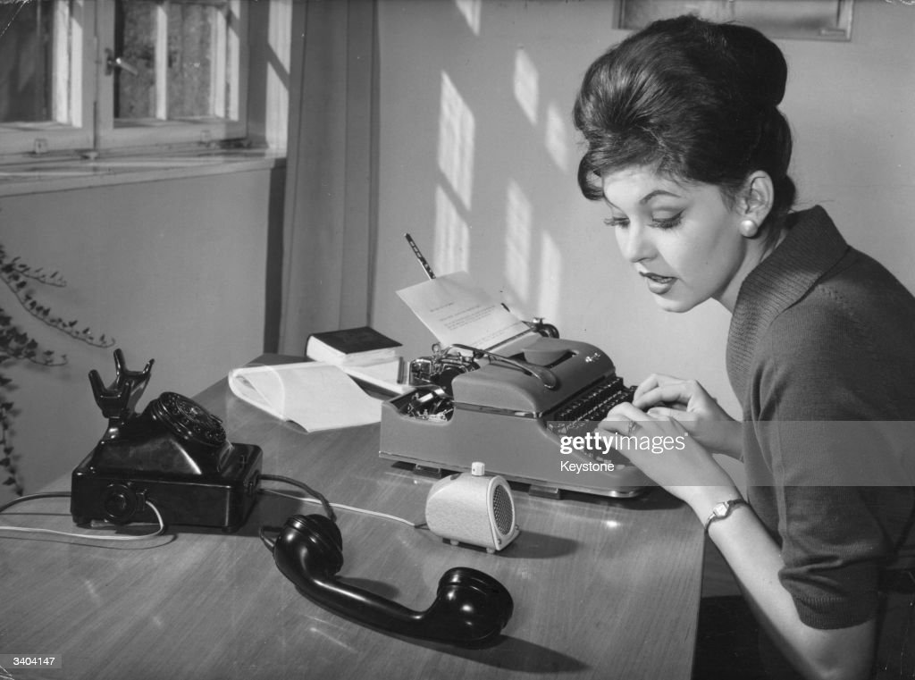 A Munich secretary simultaneously typing and making a phone call with the aid of the Beoton telephone amplifier.