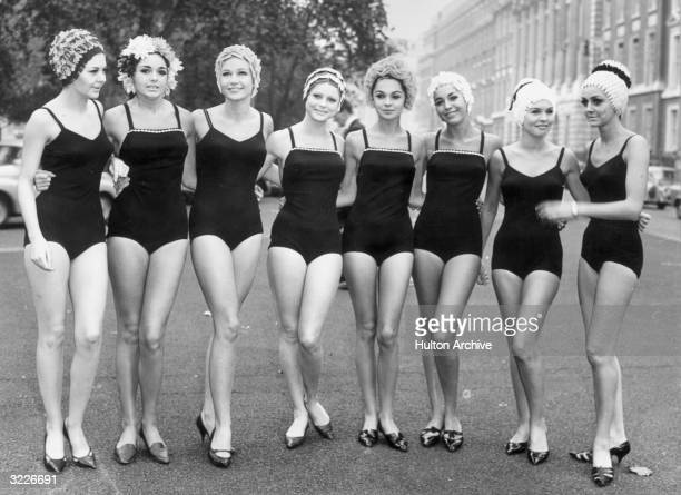 Fulllength image of eight women standing arminarm on a street modeling onepiece Kleinert swimsuits and bathing caps London England