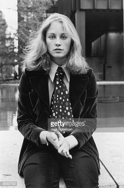 Portrait of American actor and model Cybill Shepherd sitting on a concrete wall in front of a fountain and rubbing her hands together New York City...
