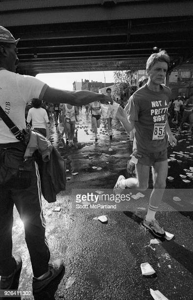 New York A volunteer with the New York Road Runners Club hands a cup of water to a runner at the 10 mile mark on Bedford Avenue in Brooklyn during...