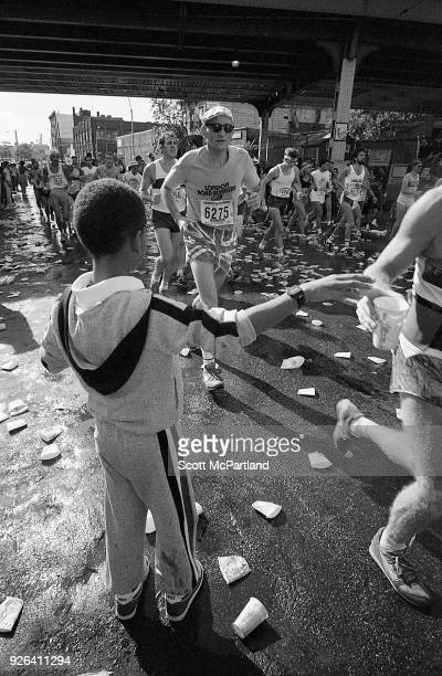 New York A young boy hands a cup of water to a passing runner at the 10 mile mark on Bedford Avenue in Williamsburg Brooklyn during the NYC Marathon