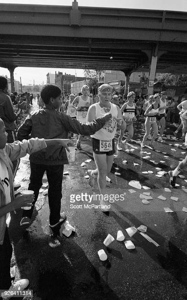 New York A young boy hands a cup of water to a passing runner at the 10 mile mark on Bedford Avenue in Brooklyn during the NYC Marathon