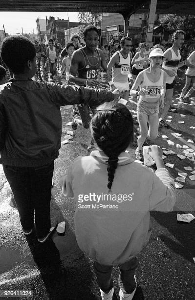 New York Children with cups of water in hand pass them to runners as they cross the 10 mile mark in Williamsburg Brooklyn during the NYC Marathon