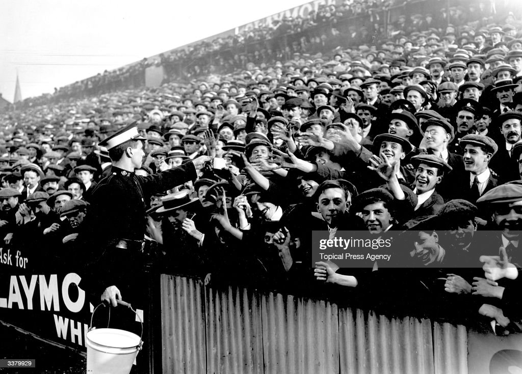An ambulance worker handing out water at a crowded football match between Tottenham Hotspur and Manchester City at White Hart Lane in London.