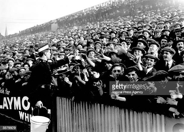 An ambulance worker handing out water at a crowded football match between Tottenham Hotspur and Manchester City at White Hart Lane in London