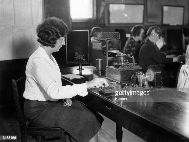 An employee at the Central Telegraph Office of the General Post Office in London using the Morse Code hand system soon to be replaced by the teletype...