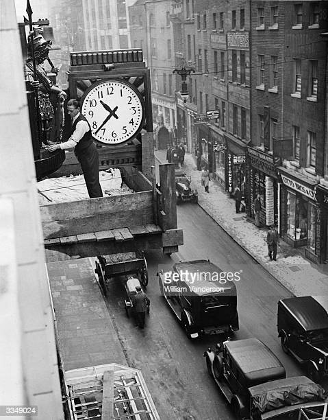 Clocksmith putting the finishing touches to a replica of a 'Gog And Magog' clock as it is mounted above Cheapside, the City of London after the...