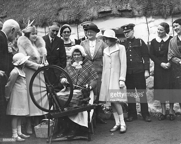 Queen Elizabeth Queen Consort to King George VI with Princesses Elizabeth and Margaret Rose watching a spinner at work in a Scottish Highland village