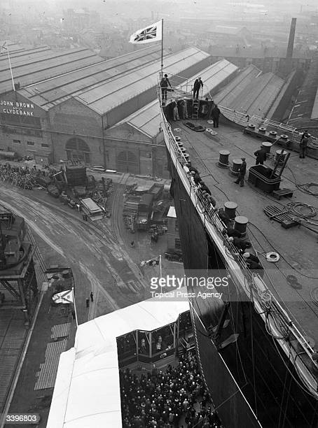 The giant bows of the 'Queen Elizabeth' tower above the shipyard before the Cunard White Star liner is launched from the John Brown Co shipyard at...
