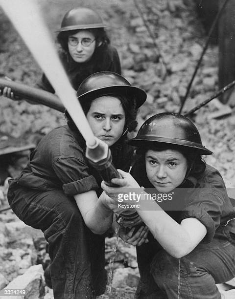 A team of firewomen belonging to the Royal Northern Hospital in Holloway train their hose on an imaginary fire during practice for Blitz fires