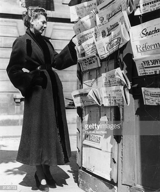 Woman wearing a Christian Dior overcoat at a news-stand.