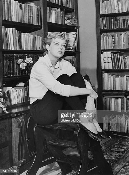 * Schauspielerin Din ihrer hauseigenen Bibliothek auf einemHocker sitzend ohne Jahr