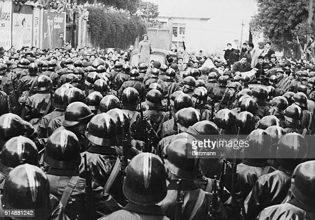 2/8/1956Algiers Algeria A lone woman demonstrator standing on rear of car and other members of an unruly Algerian mob hold off a large force of...