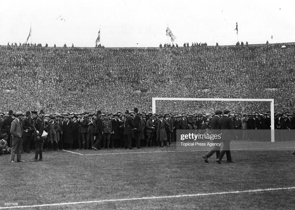 Crowds on the pitch before the FA Cup Final between West Ham United and Bolton Wanderers at Wembley Stadium, in north London. It was the first final to be held at the newly completed Stadium, with an estimated attendance of 200,000. Bolton Wanderers won the day with a 2-0 victory.