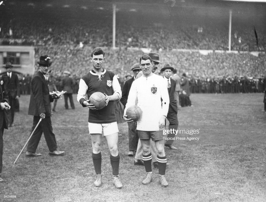 G Kay, captain of West Ham United, and Joe Smith, captain of Bolton Wanderers, on the pitch before the start of the FA Cup Final at Wembley Stadium, London.