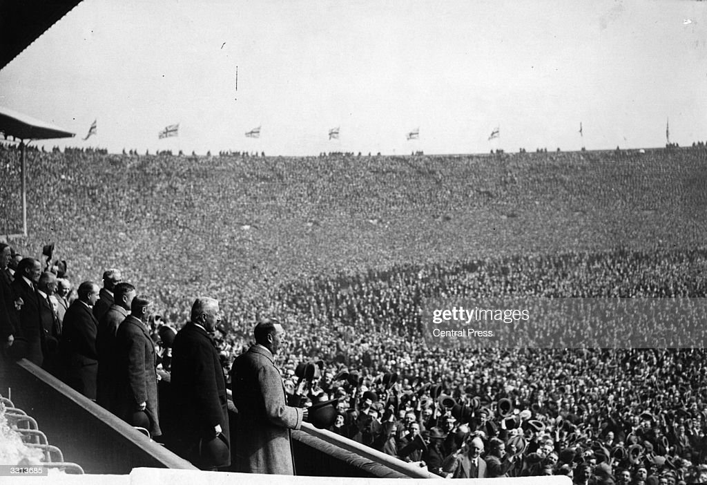 King George V (1865 - 1936) and a huge crowd attend the first FA Cup Final to be held at Wembley Stadium, London, between West Ham United and Bolton Wanderers. Bolton Wanderers won the match 2-0.