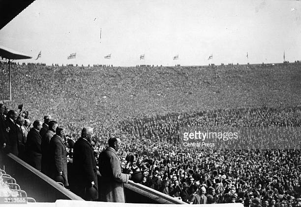 King George V and a huge crowd attend the first FA Cup Final to be held at Wembley Stadium, London, between West Ham United and Bolton Wanderers....