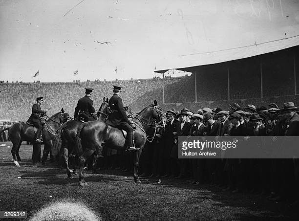 Mounted police push back the unexpectedly large crowds that have spilled onto the pitch for the first ever FA Cup final to be held at the newly...