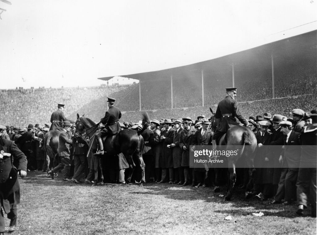 Police on horseback controlling the crowd at the FA Cup Final between West Ham United and Bolton Wanderers at Wembley Stadium, north London. It was the first final to be held there with an estimated attendance of 200,000.